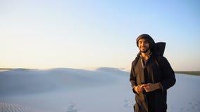 O homem feliz do emirado anda em subúrbios do deserto com sorriso na cara na noite clara do verão video estoque