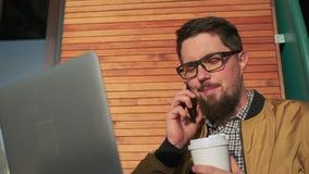 O homem feliz está falando pelo ar livre móvel no dia ensolarado, guardando a caixa com café filme
