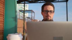 O homem feliz está relaxando apenas com o caderno na varanda aberta video estoque