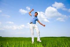 O homem feliz está saltando em um campo Fotos de Stock Royalty Free