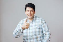 O homem feliz faz um polegar do gesto acima, retrato no fundo branco Imagem de Stock Royalty Free