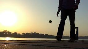 O homem feliz joga com uma bola em um banco de rio no por do sol no slo-mo filme