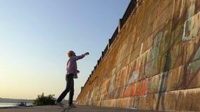 O homem feliz joga uma bola em uma parede do banco de rio no slo-mo video estoque