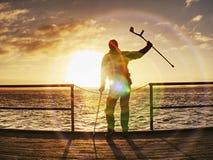 O homem feliz na ponte que guarda seu antebraço crutches Gesto da liberdade fotografia de stock