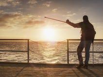 O homem feliz na ponte que guarda seu antebraço crutches Gesto da liberdade imagens de stock