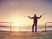 O homem feliz na ponte que guarda seu antebraço crutches Gesto da liberdade fotos de stock