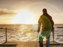 O homem feliz na ponte que guarda seu antebraço crutches Gesto da liberdade foto de stock royalty free