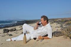 O homem feliz na praia está bebendo o vinho tinto Foto de Stock