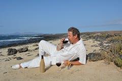 O homem feliz na praia está bebendo o vinho tinto e está esperando sua mulher Imagem de Stock
