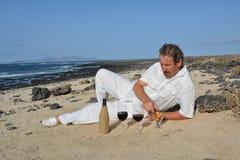 O homem feliz na praia tem dois vidros do vinho tinto Foto de Stock