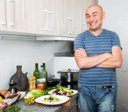 O homem feliz na prima de vida na cozinha preparou duas saladas imagens de stock royalty free