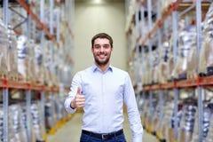 O homem feliz no armazém que mostra os polegares levanta o gesto Fotografia de Stock