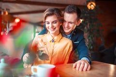 O homem feliz no terno dá aumentou à mulher bonita imagens de stock royalty free