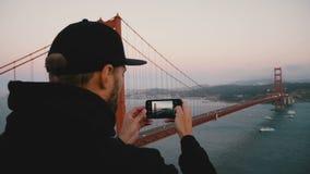 O homem feliz novo do turista da vista traseira na roupa preta toma a foto do telefone do por do sol majestoso golden gate bridge vídeos de arquivo