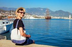 O homem feliz novo olha o porto de Alanya Viajante de sorriso que senta-se pelo mar Conceito das férias fotografia de stock royalty free