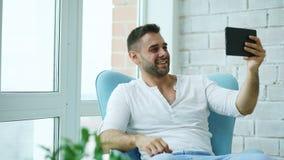 O homem feliz novo tem o bate-papo video em linha usando o tablet pc digital que senta-se no balcão no apartamento moderno do sót imagens de stock royalty free