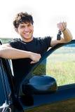 O homem feliz que mostra chaves aproxima o carro Fotografia de Stock Royalty Free