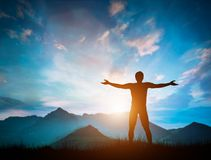 O homem feliz que olha montanhas maravilhosas ajardina no por do sol Fotos de Stock Royalty Free