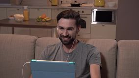 O homem feliz senta-se no sofá e tabuleta guardar nas mãos Tem tampões de ouvido nas orelhas O indivíduo está falando no skype e  video estoque