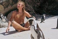 O homem feliz toma sol ao sentar-se entre pinguins fotografia de stock royalty free