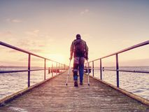 O homem ferido com revestimento encapuçado e antebraço crutches a posição na ponte do mar fotografia de stock