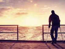 O homem ferido com revestimento encapuçado e antebraço crutches a posição na ponte do mar foto de stock royalty free