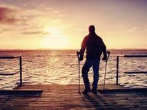 O homem ferido com revestimento encapuçado e antebraço crutches a vista tristemente imagem de stock