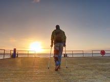 O homem ferido com revestimento encapuçado e antebraço crutches a vista tristemente imagem de stock royalty free