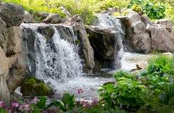 O homem fez cachoeiras em um jardim Foto de Stock