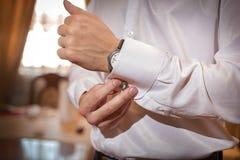O homem fixa botão de punho na camisa branca Fotografia de Stock Royalty Free