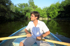 O homem flutua abaixo do rio em um barco Fotos de Stock
