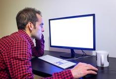 O homem focalizado olha fixamente no computador de escritório no modelo preto de madeira da mesa Camisa vermelha pontilhada, pain imagem de stock royalty free
