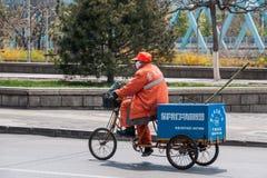 O homem folheado alaranjado no triciclo recolhe o lixo, Pequim Imagem de Stock