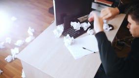 O homem forçado joga o papel amarrotado longe da tabela Movimento lento Ângulo superior video estoque