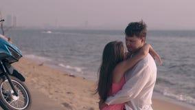 O homem forte alto abraça a jovem senhora bonita no Sandy Beach filme