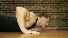 O homem forte levanta do assoalho no fitness center vídeos de arquivo