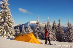 O homem forte nos sapatos de neve e nos óculos de proteção está ao lado de uma barraca amarela Fotografia de Stock Royalty Free