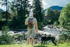 O homem forte novo fica o rio próximo das montanhas com cão e procura da vista Fotografia de Stock