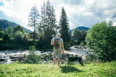 O homem forte novo fica o rio próximo das montanhas com cão e procura da vista Fotografia de Stock Royalty Free