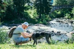 O homem forte novo fica o rio próximo das montanhas com cão e procura da vista Imagens de Stock Royalty Free