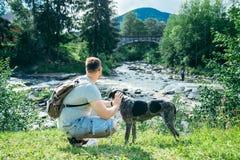 O homem forte novo fica o rio próximo das montanhas com cão e procura da vista Foto de Stock Royalty Free