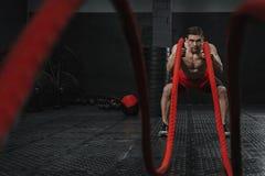 O homem forte novo que faz cordas da batalha exercita no gym do crossfit imagem de stock royalty free