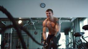O homem forte termina o exercício com cordas da batalha no gym filme