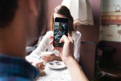 O homem fotografa a menina no café amor e tecnologia imagem de stock