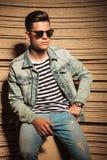 O homem fresco nas calças de brim revestimento e óculos de sol senta-se Fotos de Stock