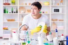 O homem frustrado em ter que lavar pratos foto de stock