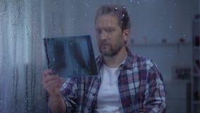 O homem frustrado que olha nos pulmões radiografa no dia chuvoso, doença incurável, câncer filme