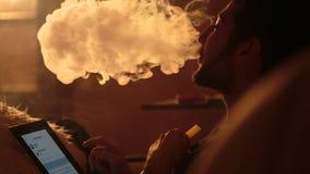 O homem fuma um cachimbo de água e usa a tabuleta imagens de stock royalty free