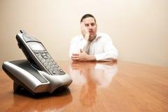 O homem furado espera o telefone Imagens de Stock
