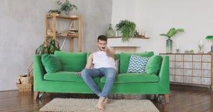 O homem furado vem na sala de visitas, senta-se no sofá verde gerencie na televisão e na observação video estoque
